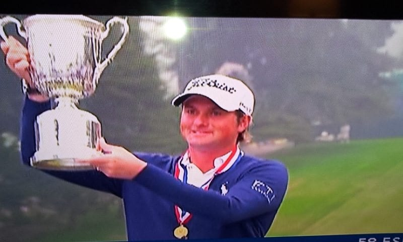 Webb Simpson lifting the US Open Trophy
